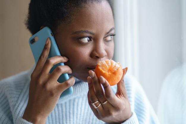 Chora afro kobieta, rozmawiająca przez telefon, próbująca wyczuć zapach pół świeżej mandarynki. covid-19