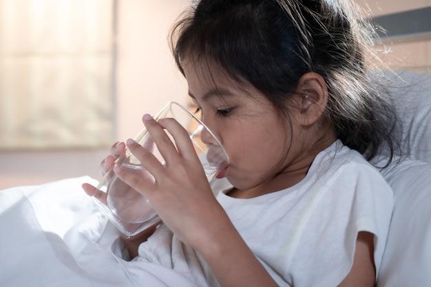 Chora azjatycka dziewczynka pije wodę ze szklanki po zjedzeniu leku w sypialni.
