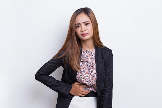 Chora azjatycka młoda kobieta biznesu z bólem brzucha na białym tle