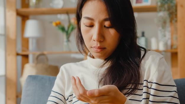 Chora azjatycka młoda kobieta trzyma pigułkę, patrząc na lekarstwo, siedząc na kanapie w domu