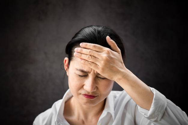 Chora azjatykcia kobieta dotyka głowę z złym czuciowym bólem głowy