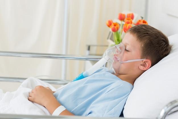 Chora chłopiec jest ubranym maskę tlenową w szpitalu