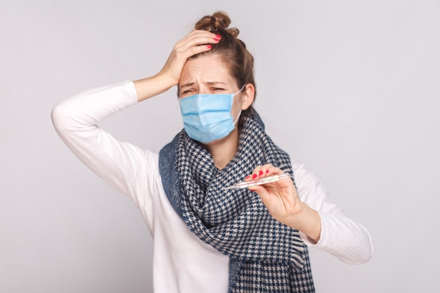 Chora chora kobieta w masce chirurgicznej, szaliku i gorączce, trzymająca głowę i smutno wyglądający termometr z wysoką temperaturą. kryty, studio strzał, na białym tle na szarym tle