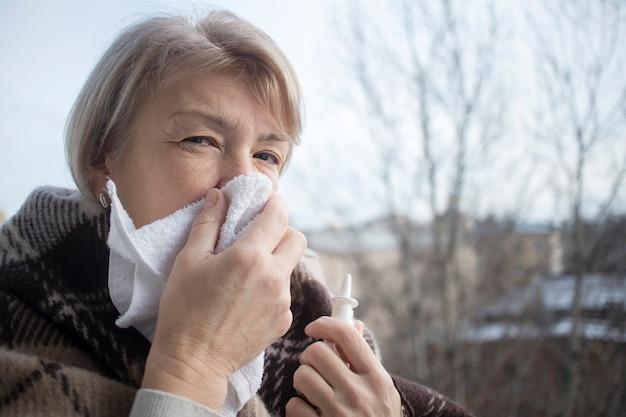 Chora chora starsza dojrzała kobieta kapie, wstrzykując do nosa kroplę zatkanego nosa. emerytowana kobieta z katarem trzyma spray medyczny, pigułki w dłoni, dmuchając nosem w chusteczkę. leczenie zapalenia zatok