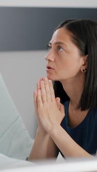 Chora córka śpi po operacji medycznej, podczas gdy zmartwiona matka modli się o leczenie choroby