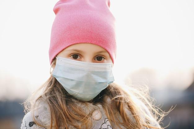 Chora dziewczyna jest ubranym ochronę podczas pandemii. ładna młoda kaukaska dziewczyna bierze na medycznej masce plenerowej. dziewczyna w masce medycznej podczas epidemii koronawirusa covid-19.