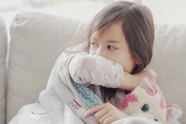 Chora dziewczyna kaszle łokciem w domu