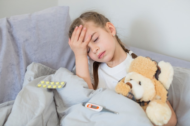 Chora dziewczyna używa termometr