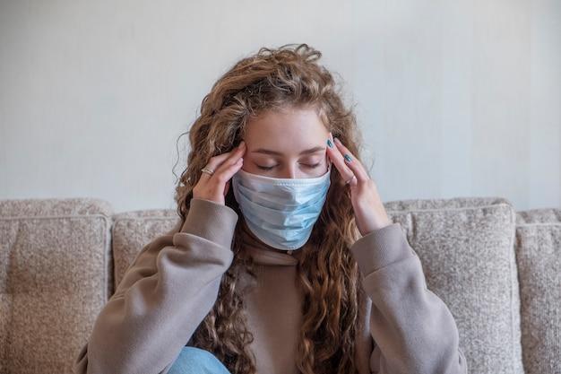 Chora dziewczyna w maski medyczne z objawem bólu głowy. koncepcja koronawirusa.