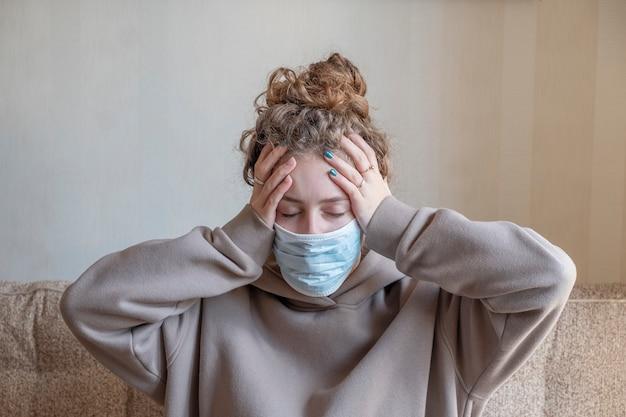 Chora dziewczyna w maski medyczne z objawem bólu głowy.