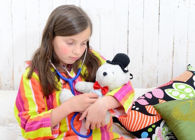 Chora dziewczynka bawi się swoim misiem