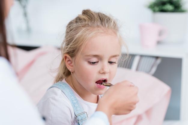 Chora dziewczynka blond biorąc lekarstwo z łyżeczki trzymanej przez lekarza w szpitalu podczas leczenia