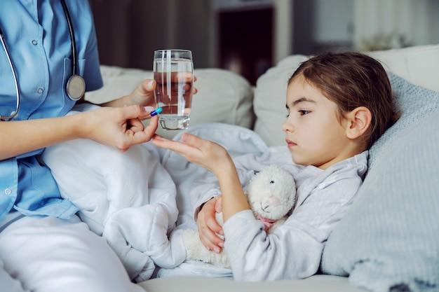 Chora dziewczynka leży na kanapie w domu i pielęgniarka daje jej pigułkę