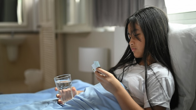 Chora dziewczynka w kocu leży na łóżku i bierze pigułkę.