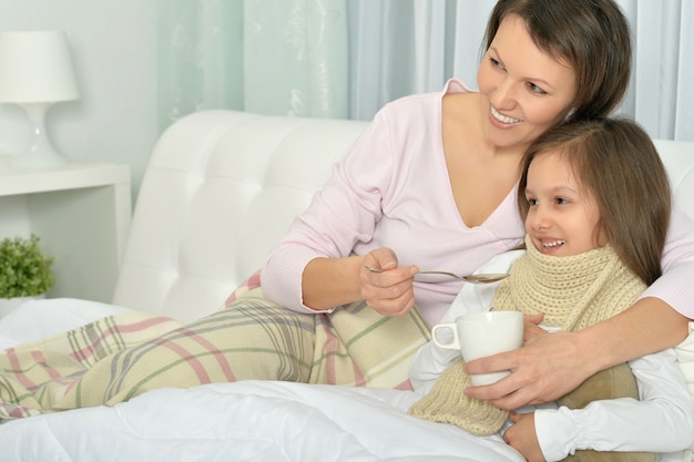 Chora dziewczynka z mamą w łóżku z gorącym napojem w domu