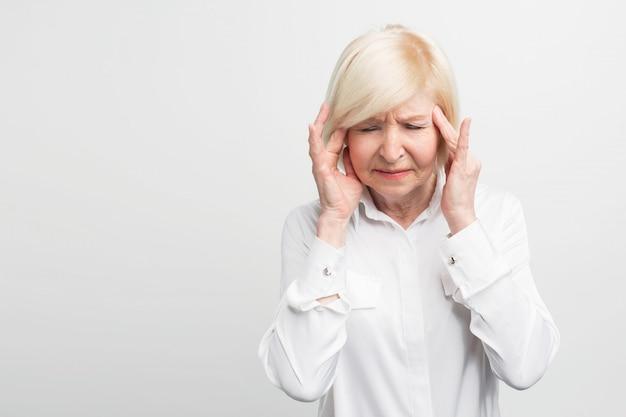 Chora i stara kobieta dotyka głowy, pokazując, że boli ją głowa. prawdopodobnie zachoruje. ścieśniać.