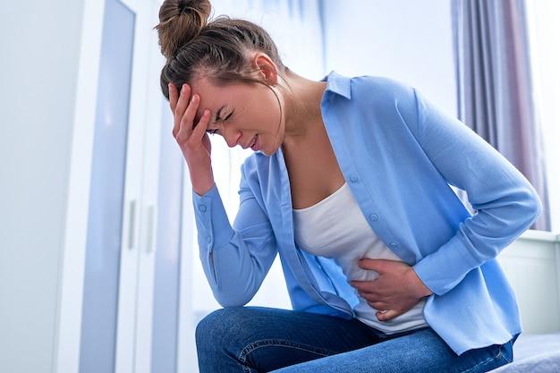 Chora kobieta cierpiąca na pms i ból menstruacyjny.