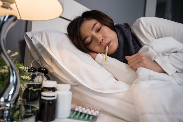 Chora kobieta czuje się zimno i za pomocą termometru sprawdza swoją temperaturę w łóżku
