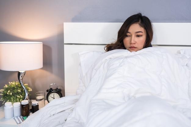Chora kobieta czuje się zimno w koc na łóżku w domu