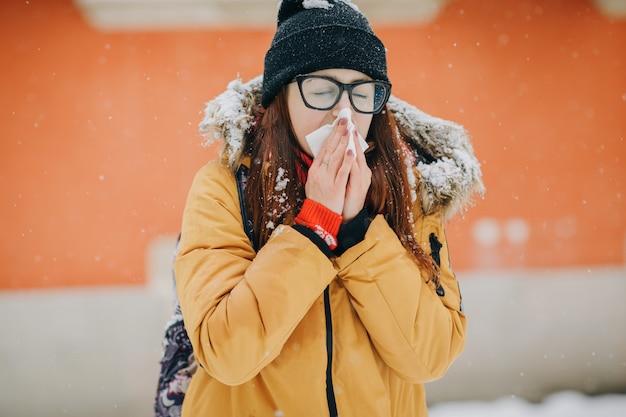 Chora kobieta dmuchanie nosa w tkankę na zewnątrz