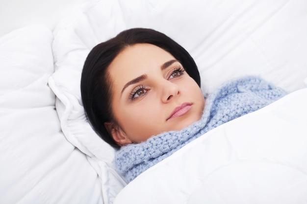 Chora kobieta. grypa. dziewczyna z zimnym leżącym pod kocem trzymającym chusteczkę