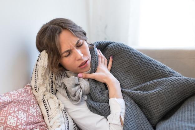 Chora kobieta, leżąc na kanapie i drży