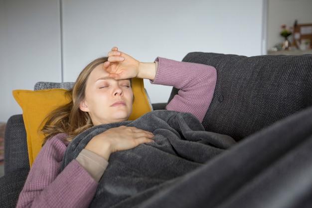 Chora kobieta leży na szarej kanapie w domu, trzymając ręce na piersi