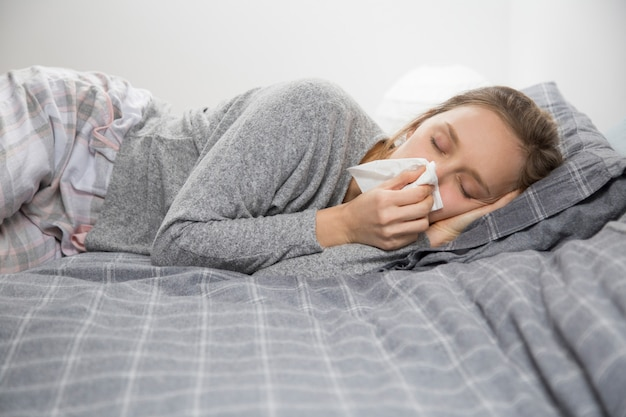 Chora kobieta leży w łóżku z zamkniętymi oczami, dmuchający nos