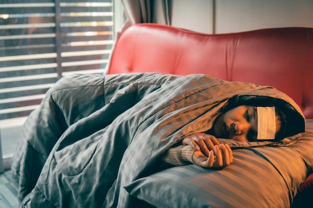 Chora kobieta ma przeziębienie i śpi na kanapie, selektywna i miękka ostrość.