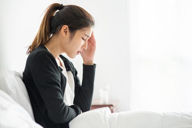 Chora kobieta miała ból głowy, a ręce dotykały jej głowy na łóżku.