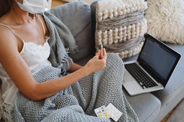 Chora kobieta nosi maskę ochronną, siedzi na kanapie z laptopem i trzyma termometr i pigułki podczas domowej izolacji kwarantanny.