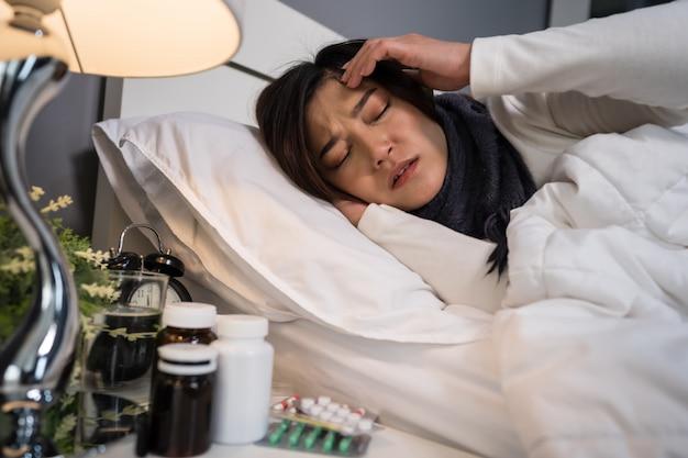 Chora kobieta odczuwa ból głowy w łóżku