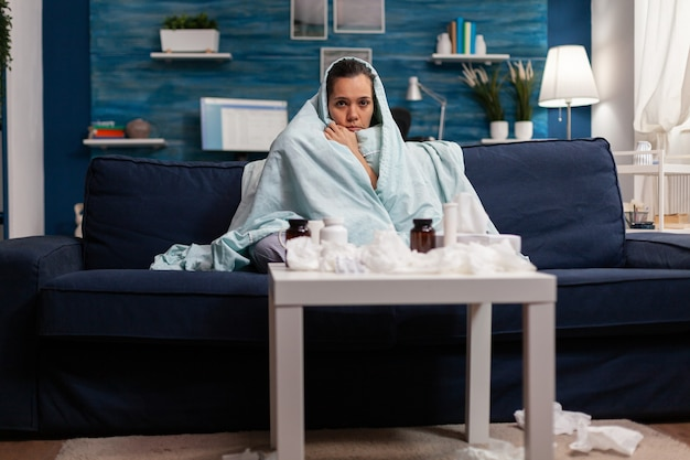Chora kobieta owinięta kocem na kanapie w domu czuje się zimno chora na chorobę wirusową choroba choroba s...