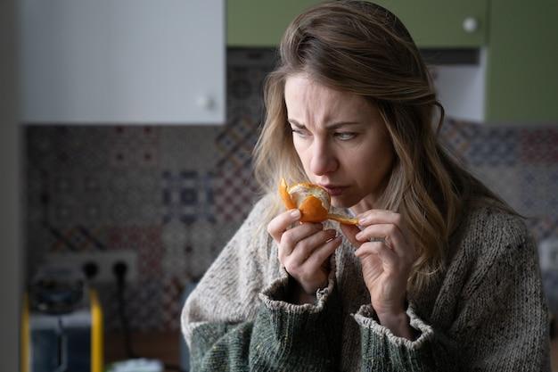 Chora kobieta próbująca wyczuć zapach świeżej pomarańczy mandarynkowej, ma objawy wirusa koronowego covid-19