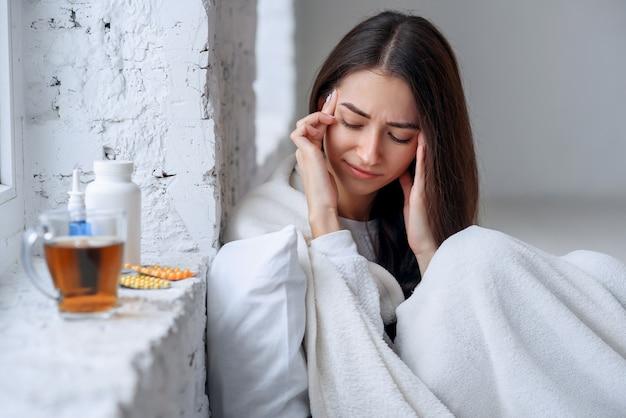 Chora kobieta przeziębiła się, czuła chorobę i kichała w papierowym ścieraniu