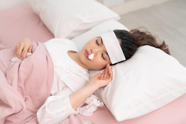Chora kobieta, przykryta kocem, leżąca w łóżku z wysoką gorączką i grypą, odpoczywa.