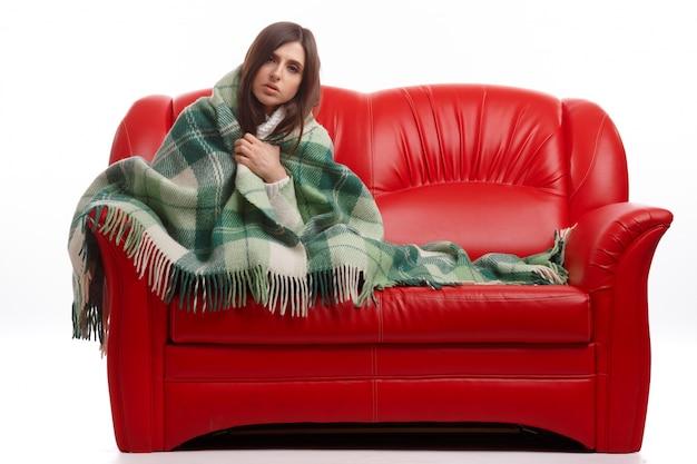 Chora kobieta siedzi na kanapie z kocem
