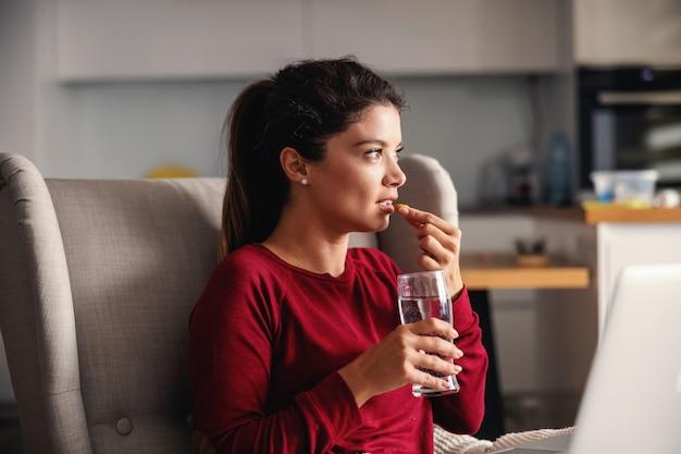 Chora kobieta siedzi w domu podczas blokady i zażywa tabletki