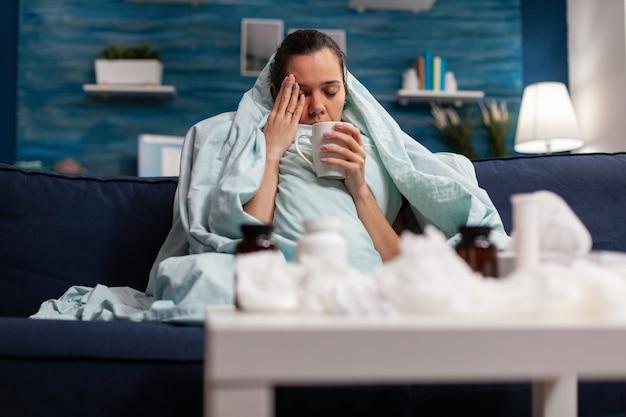 Chora kobieta siedzi w domu w kocu z gorącą herbatą