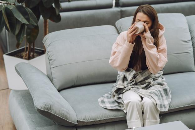 Chora kobieta siedzi w domu z bólem głowy