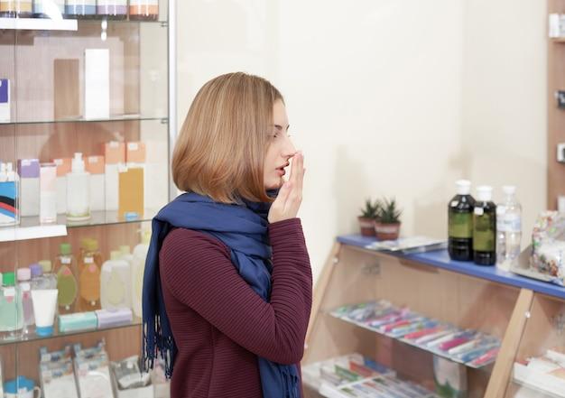 Chora kobieta szuka leków na choroby w aptece.