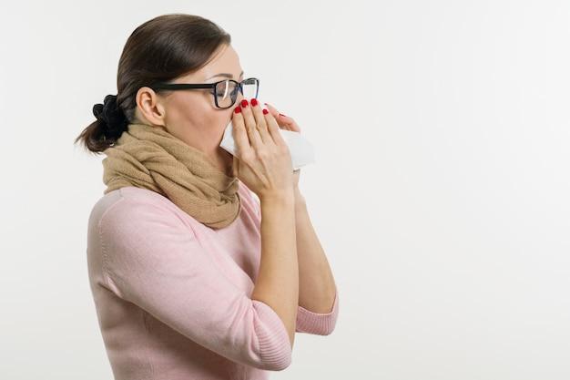 Chora kobieta trzyma chusteczkę, białe tło