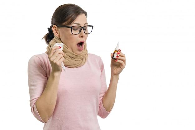 Chora kobieta trzyma chusteczkę i spray do nosa