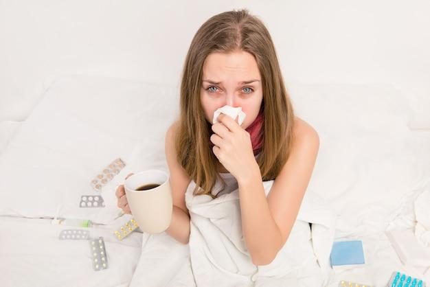 Chora kobieta trzyma kubek gorącej herbaty