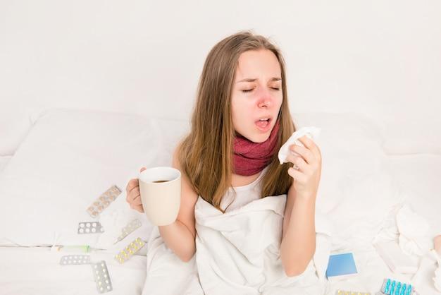 Chora kobieta, trzymając kubek gorącej herbaty i ziewanie