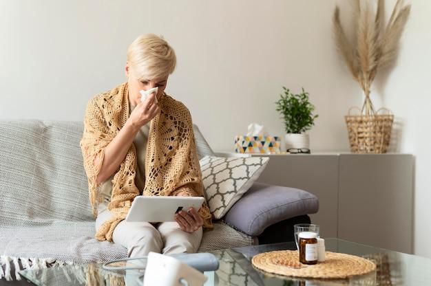 Chora kobieta trzymająca tablet średni strzał