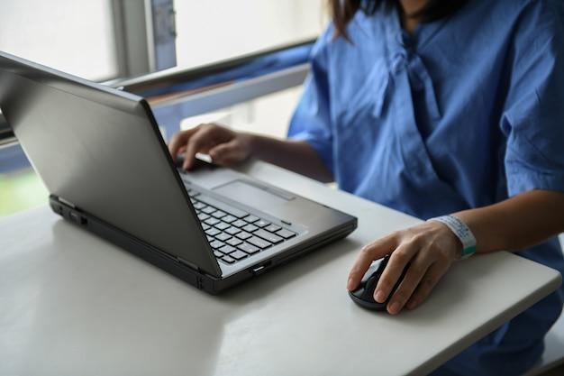 Chora kobieta używa laptop pracować na stole.