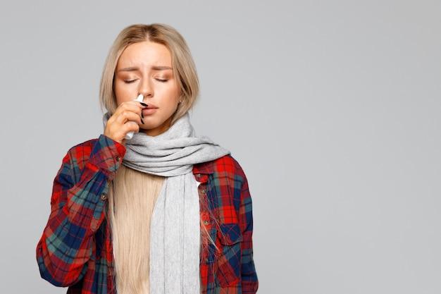 Chora kobieta używa sprayu do nosa, aby sobie pomóc