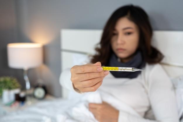 Chora kobieta używa termometr i pokazuje wysoką temperaturę w łóżku