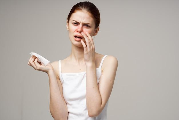 Chora kobieta w białej koszulce z jasnym tłem szalika